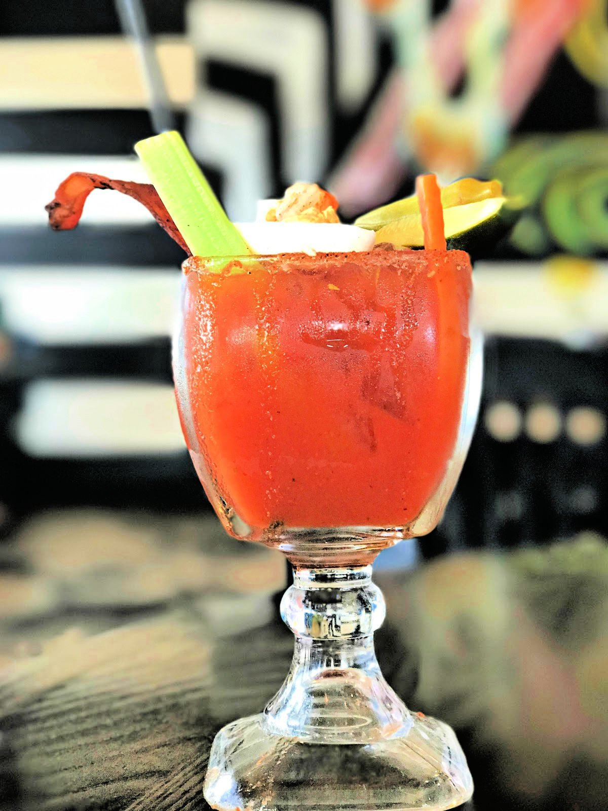 A bloody Mary with celery stalk, bacon, and pickled vegetables.