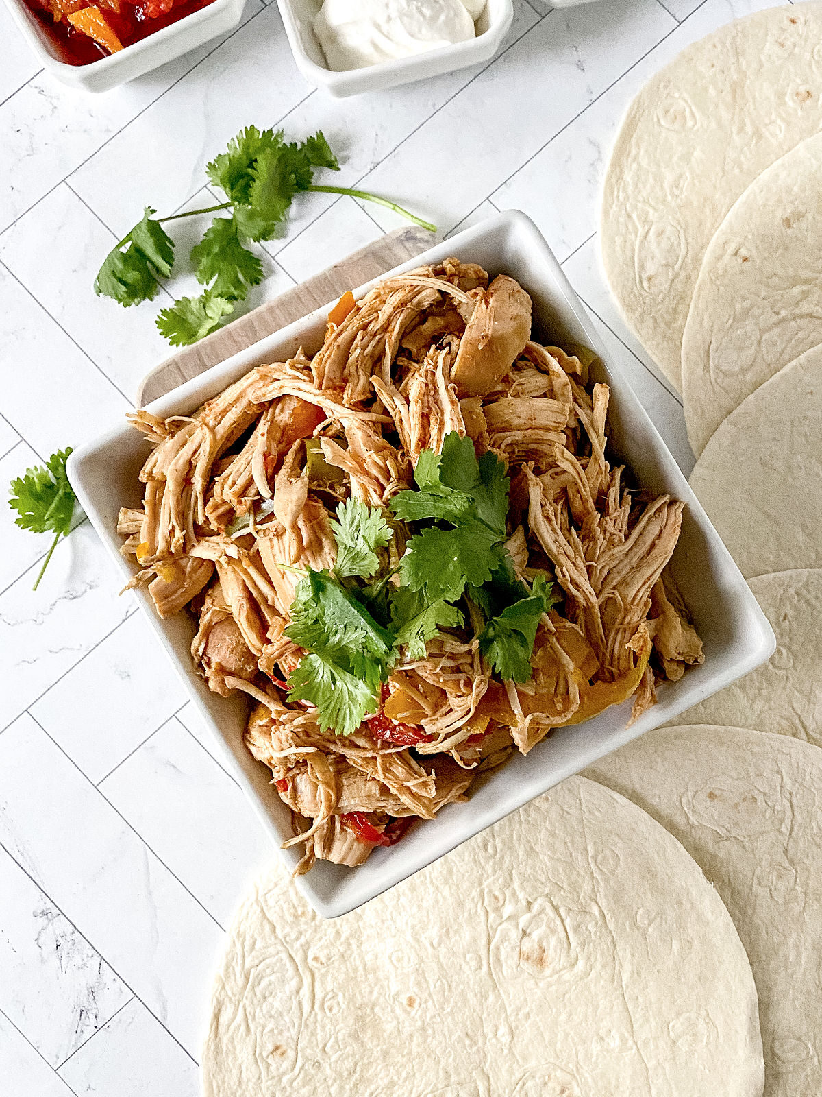 Bowl of shredded chicken topped with cilantro.