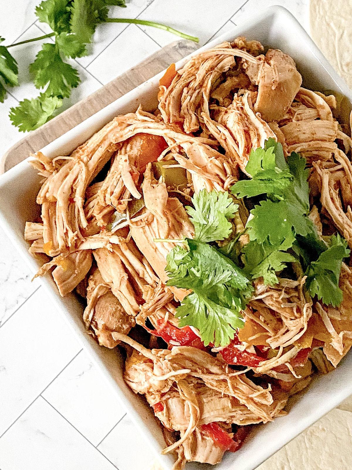 Bowl of shredded chicken seasoned with fajita seasonings.