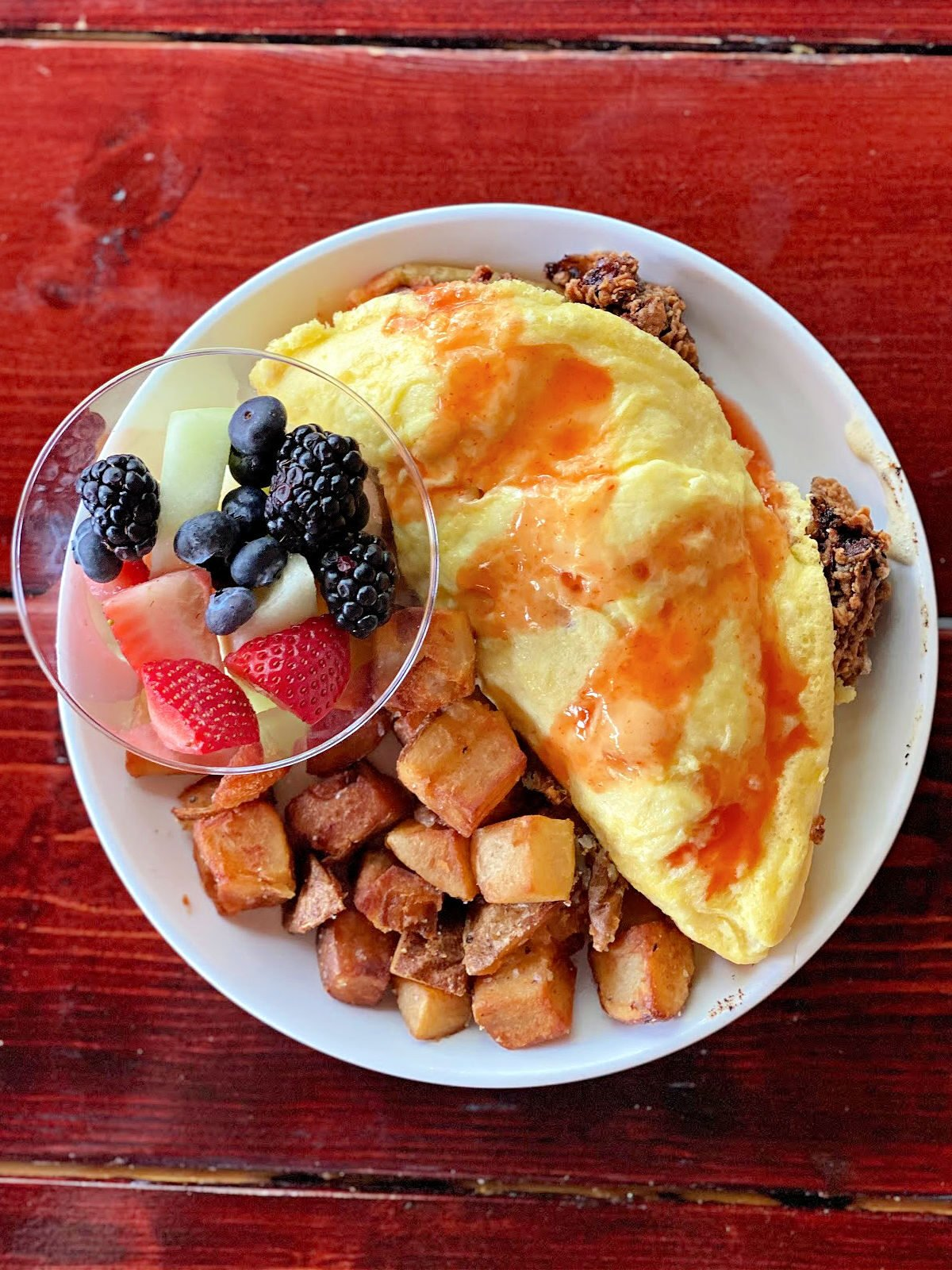 Chicken omelette with waffle pieces, roasted potatoes, and cup of fruit.