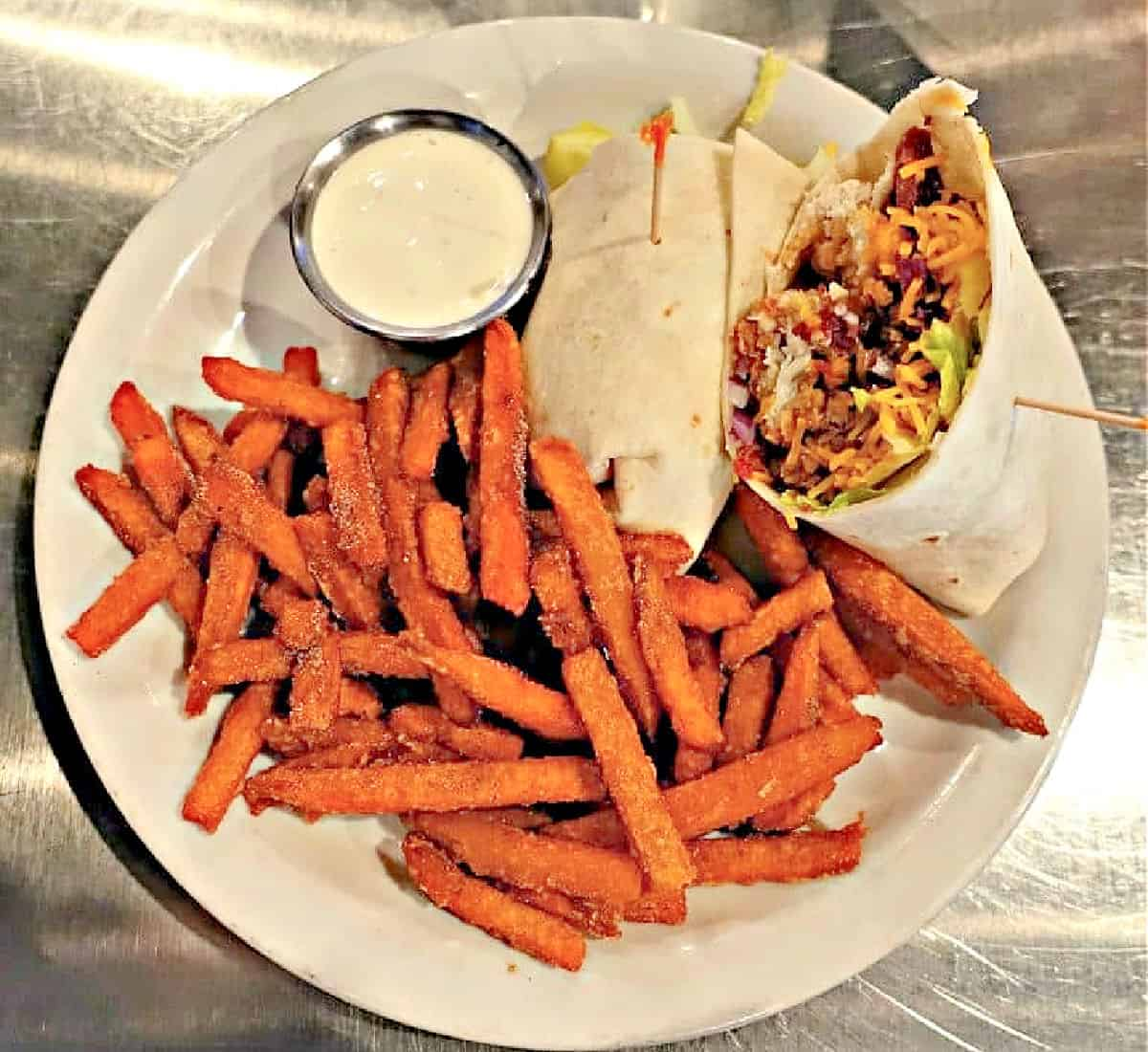 Plate with chicken wrap and side of sweet potato French fries.