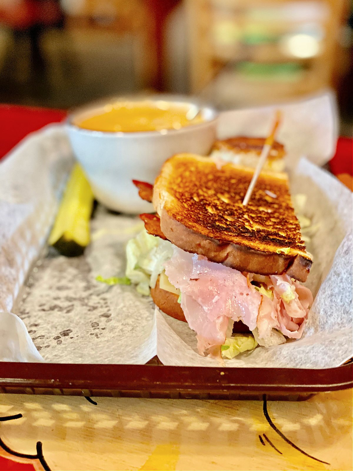 Club sandwich on a tray with a cup of beer cheese soup.