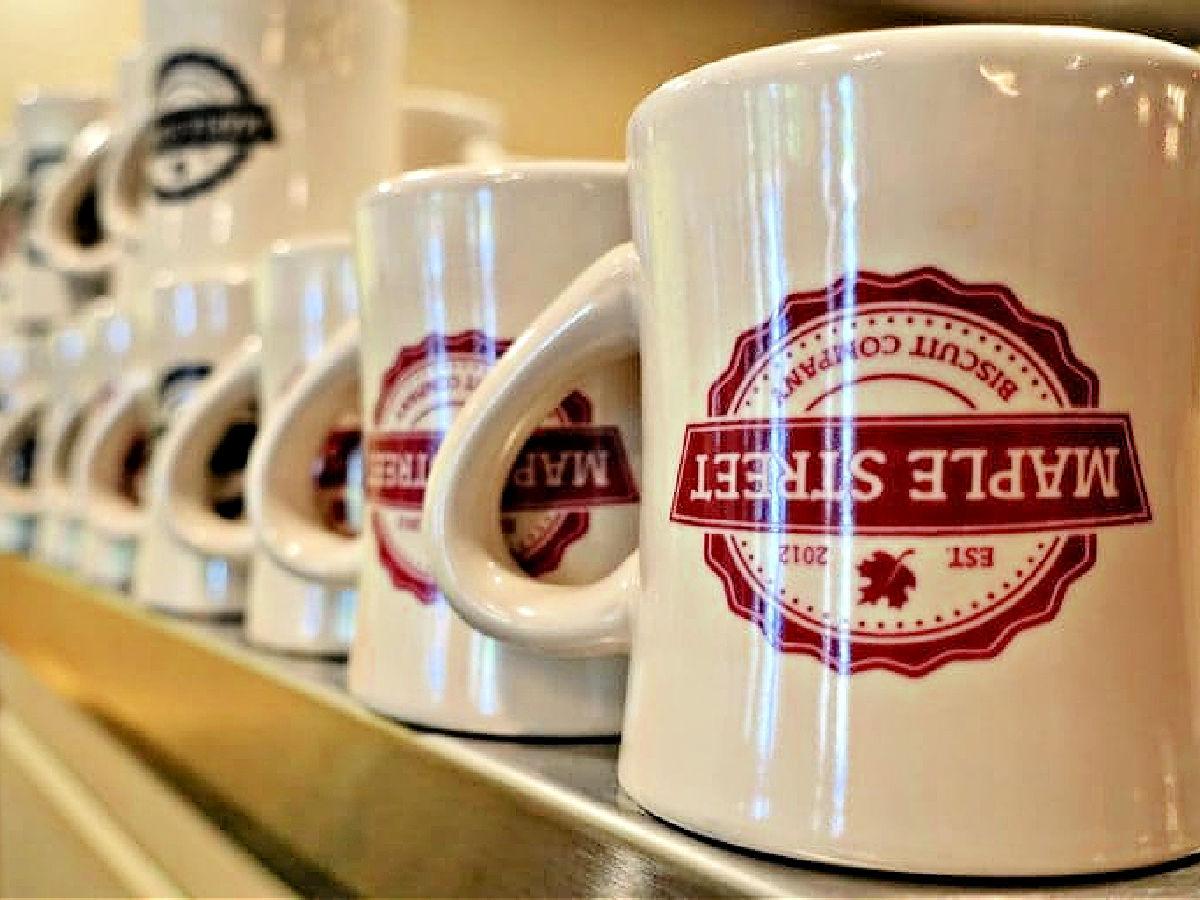 Row of Maple Street coffee mugs on a shelf.