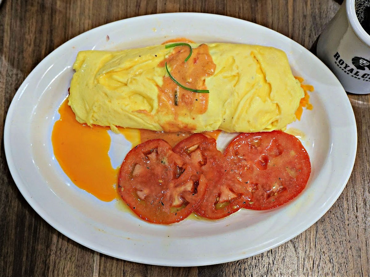 Creole omelette on a plate topped with an orange sauce and served with sliced tomatoes.