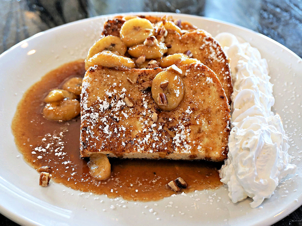 Plate of French toast topped with bananas with whipped cream.