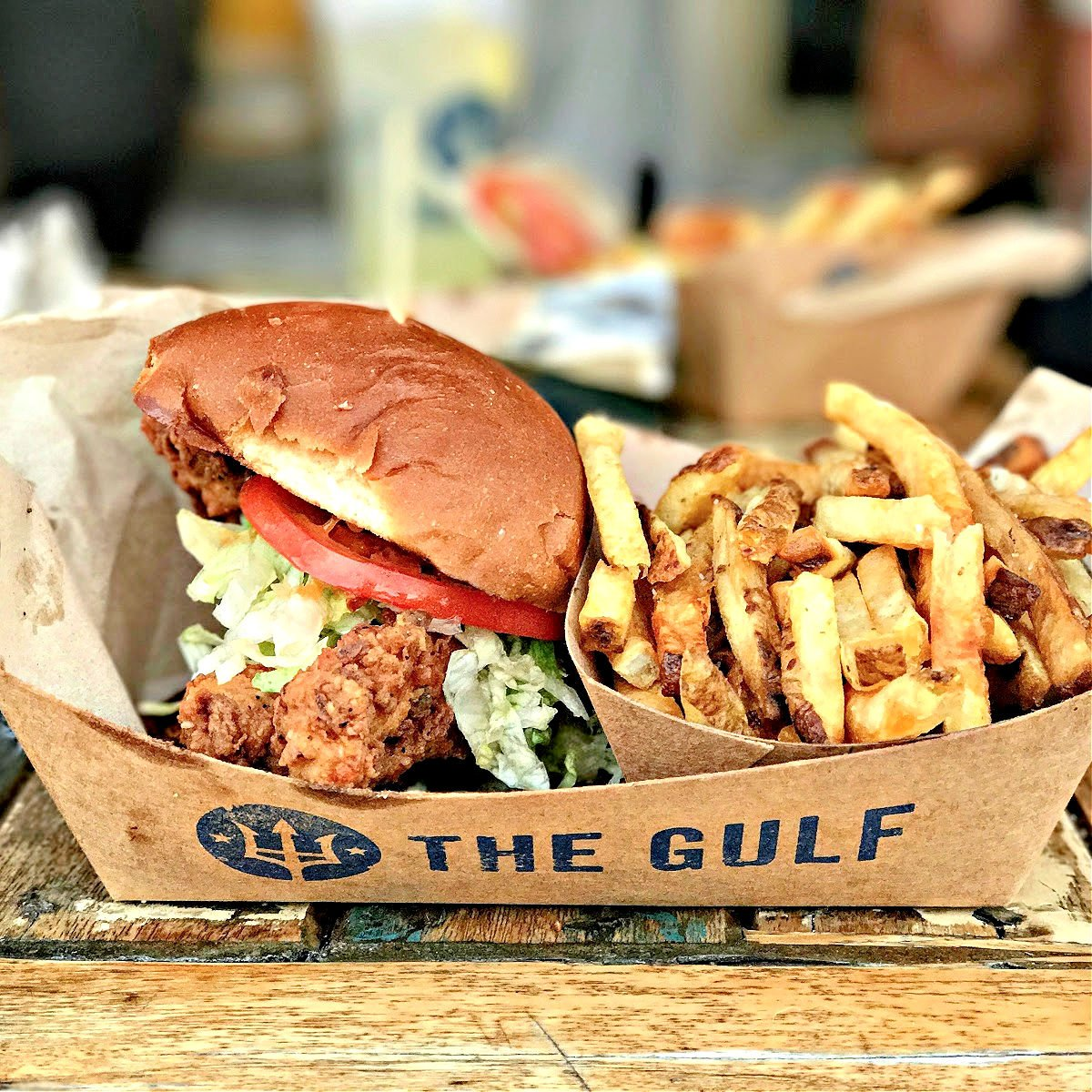 Fried fish sandwich with a side of French fries.