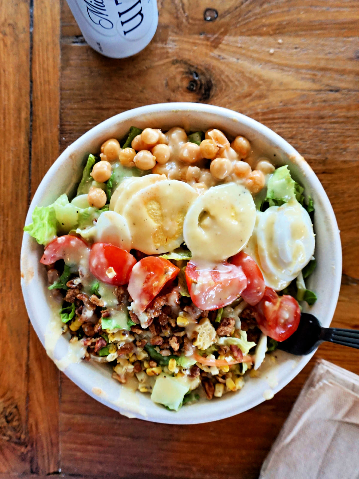 Bowl of grains, chick peas, tomatoes, cucumbers, lettuce, and hard boiled eggs.