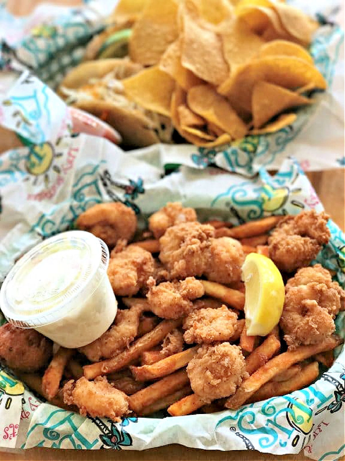A basket of fried shrimp and French fries and slice of lemon.