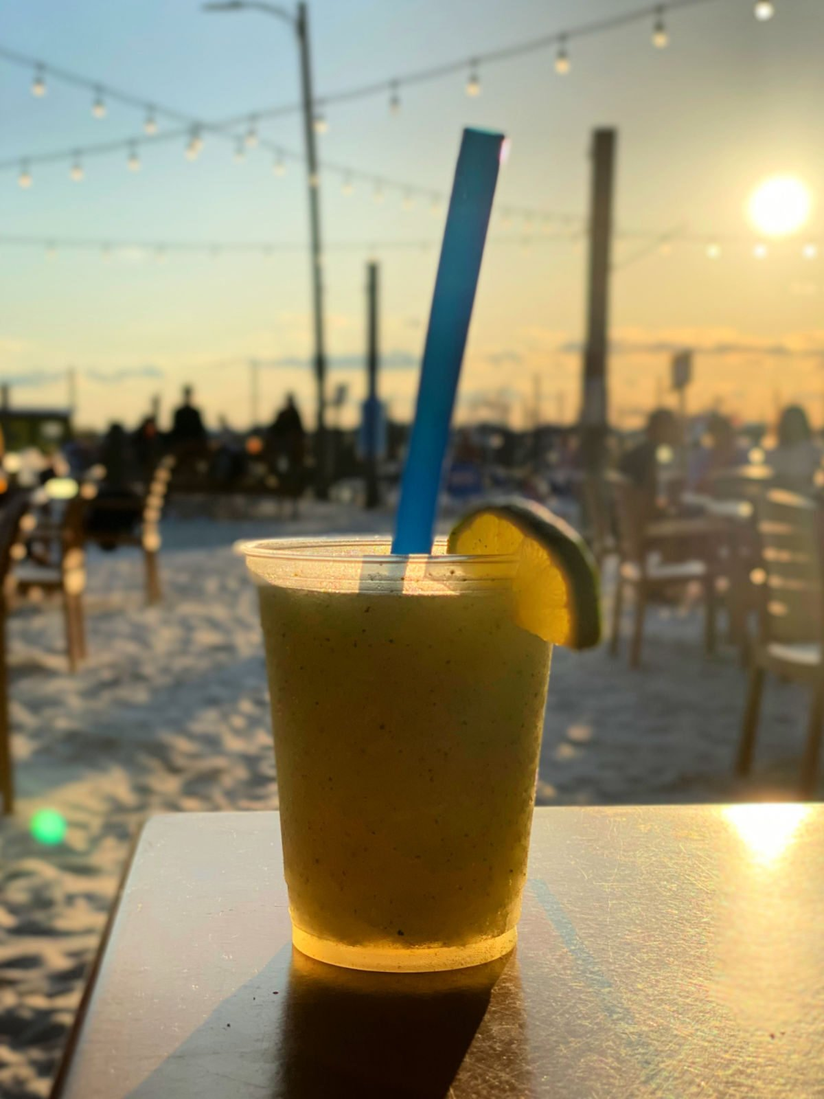 A small mojito on a table with the sun setting in the background.