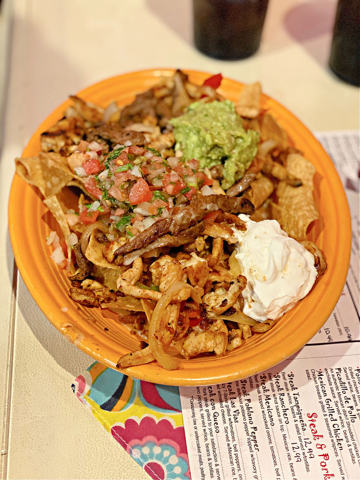 Plate of ultimate nachos with sour cream and guacamole.