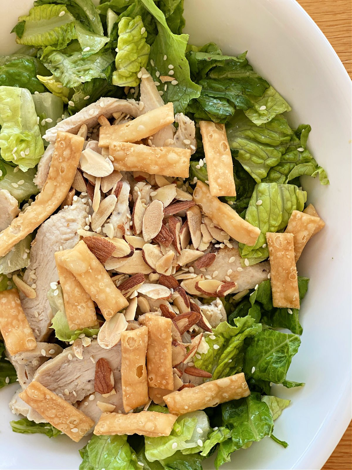 Close up view of Panera's Asian Sesame Salad with crispy wontons and slivered almonds.