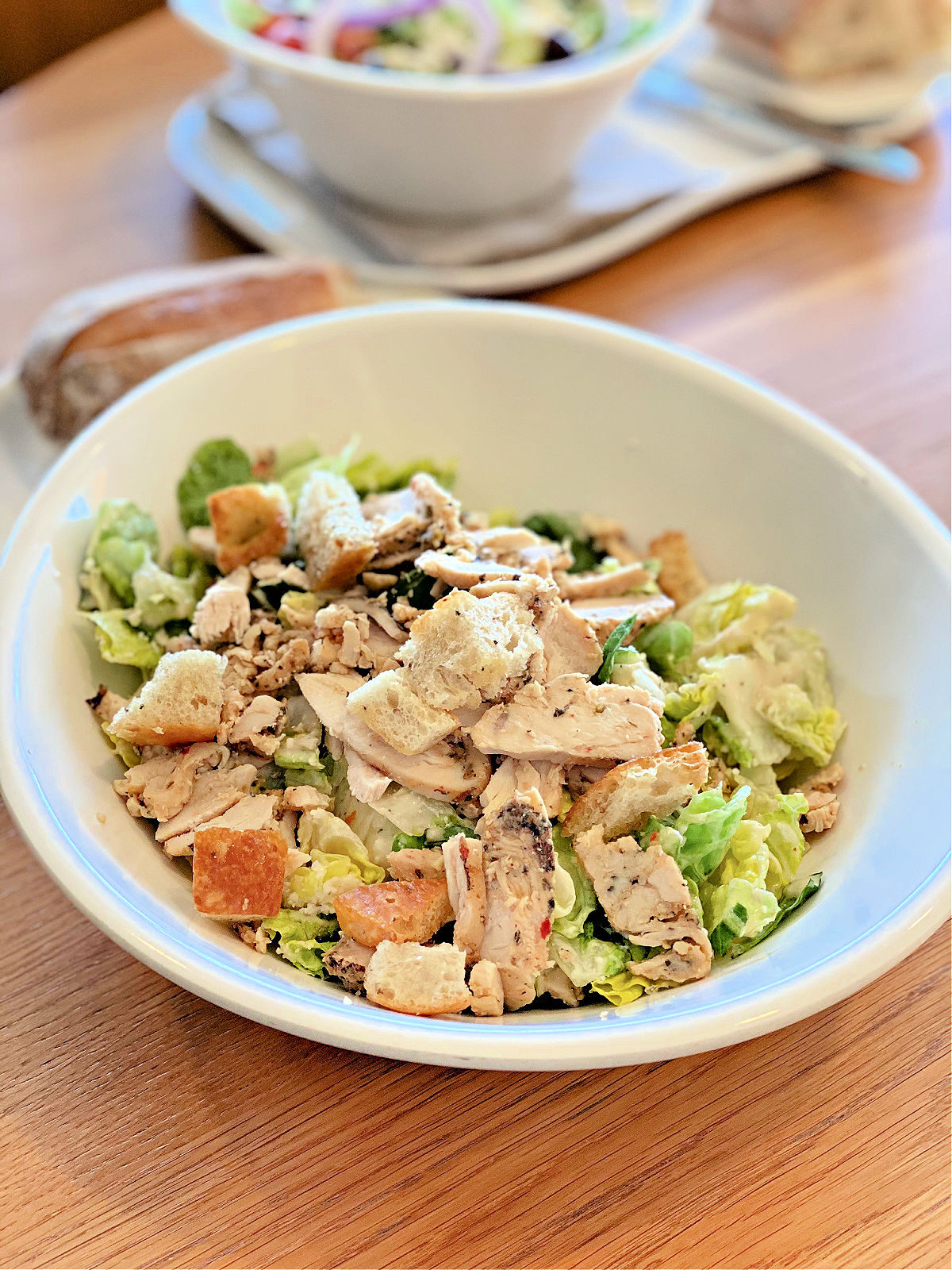 Bowl of Panera's Chicken Caesar Salad and some French bread.