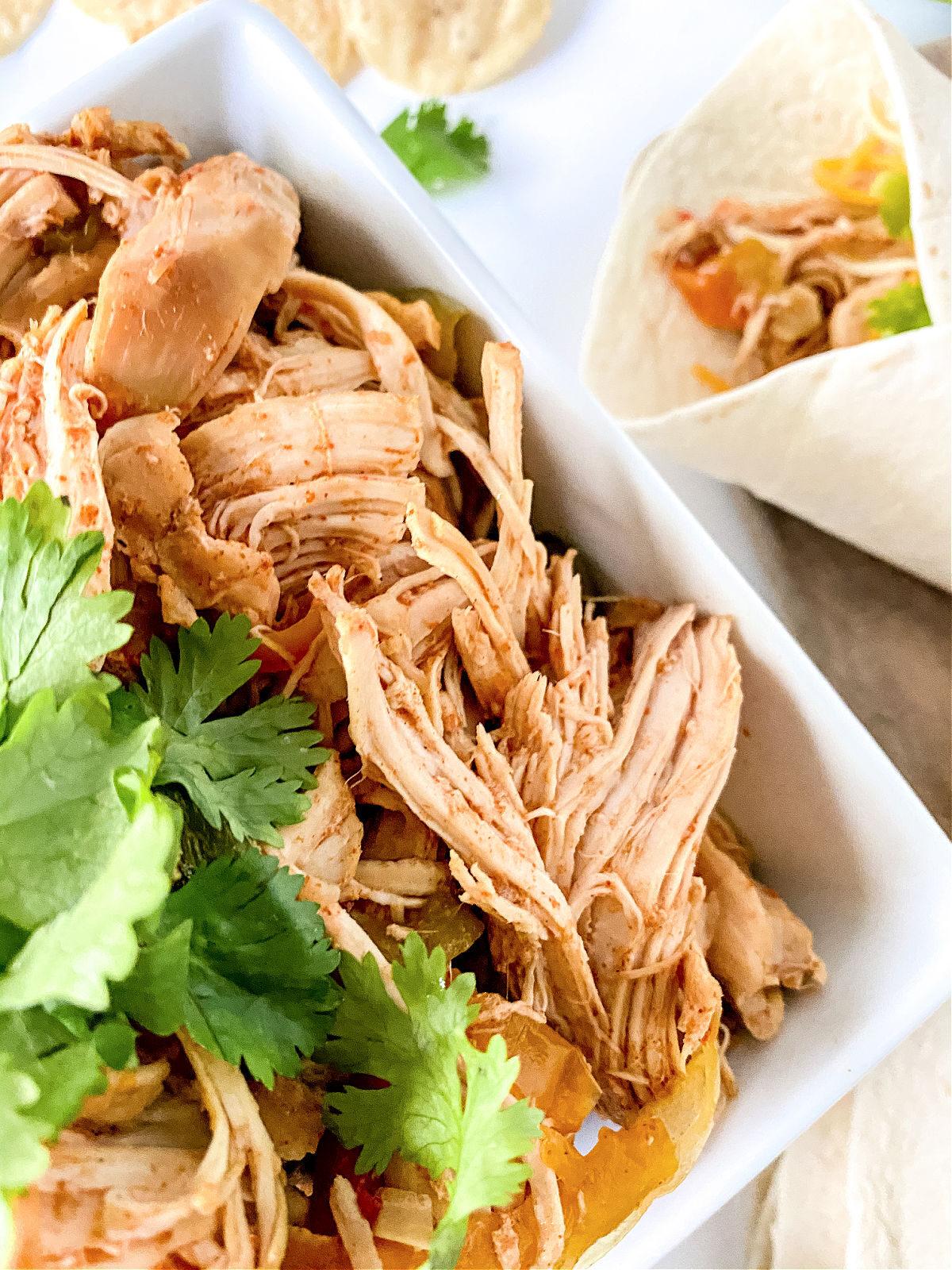 Bowl of chicken fajita meat and wrapped chicken fajita.