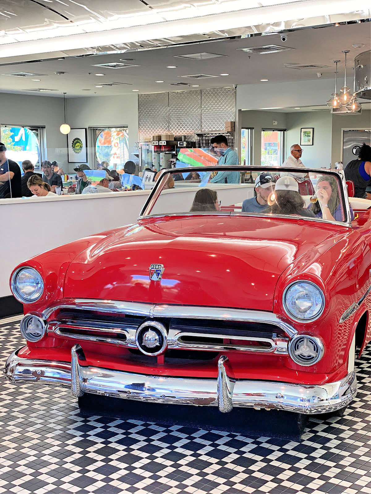 Antique red car being used as a dining booth.
