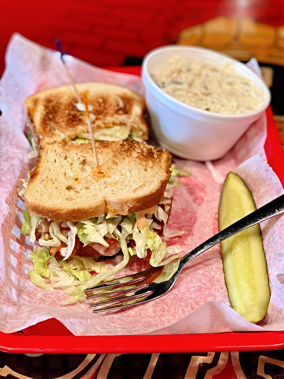 Basket with Smokey Joe Sandwich, a pickle spear, and cup of potato salad.