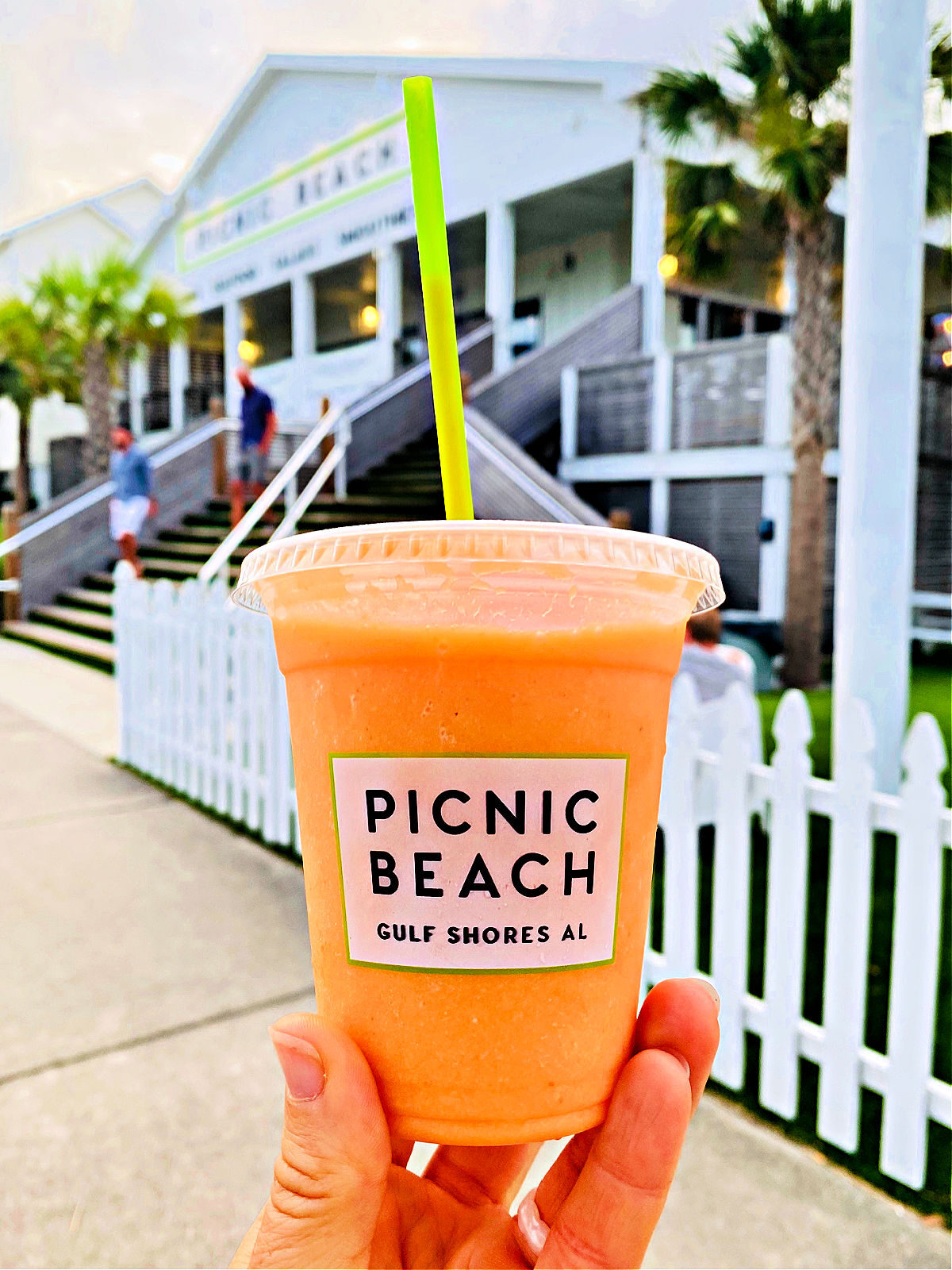 An orange smoothie be held up in front of a restaurant.
