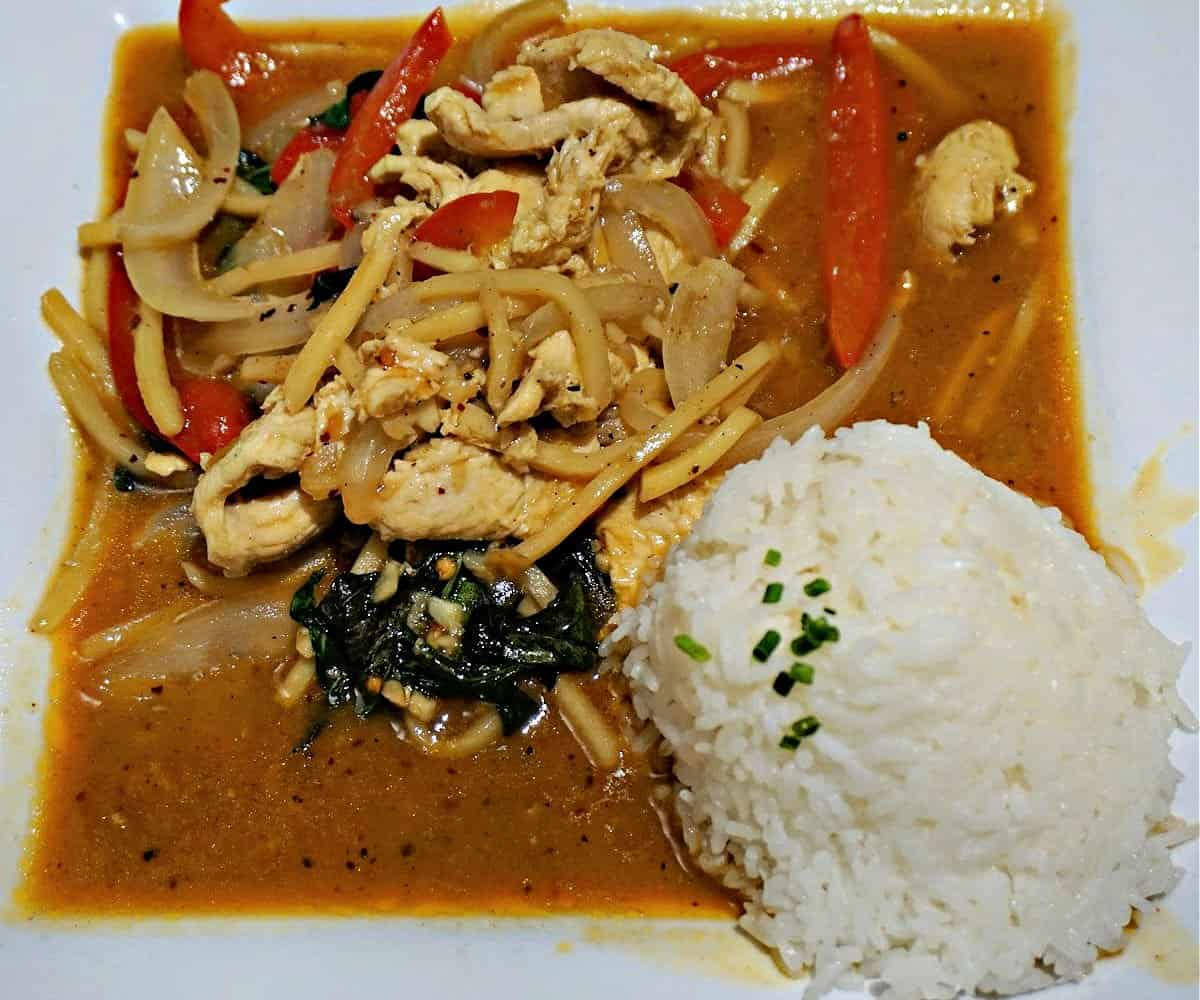 Place of spicy basil chicken and a side of white rice.