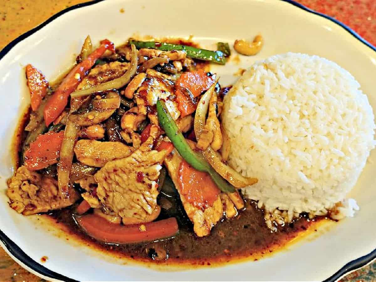 Spicy chicken with peppers, onions, and carrots with a side of white rice.