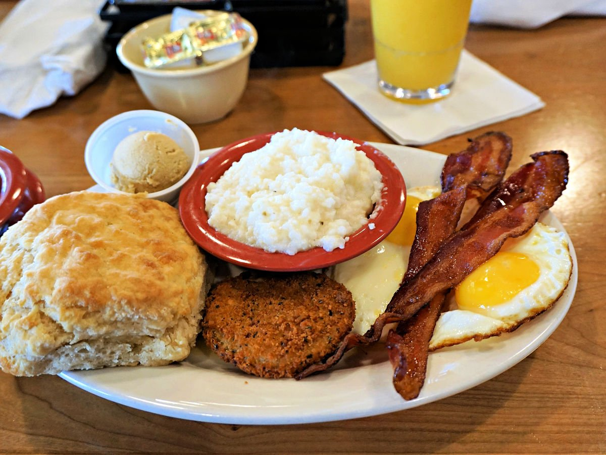 A plate with a biscuit, sausage, bacon, eggs, and grits.
