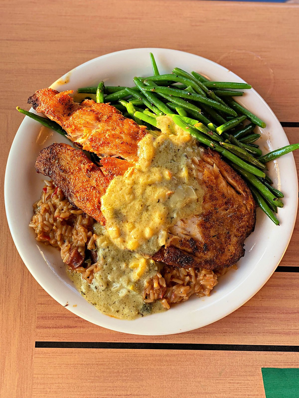 A plate with triple tail, green beans, and seasoned rice.