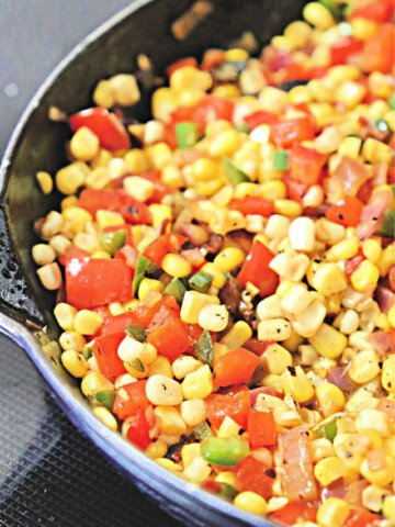 Cast iron skillet filled with corn, bacon, and tomatoes.