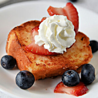 Slice of toasted angel food cake on a white plate with blueberries and strawberries.