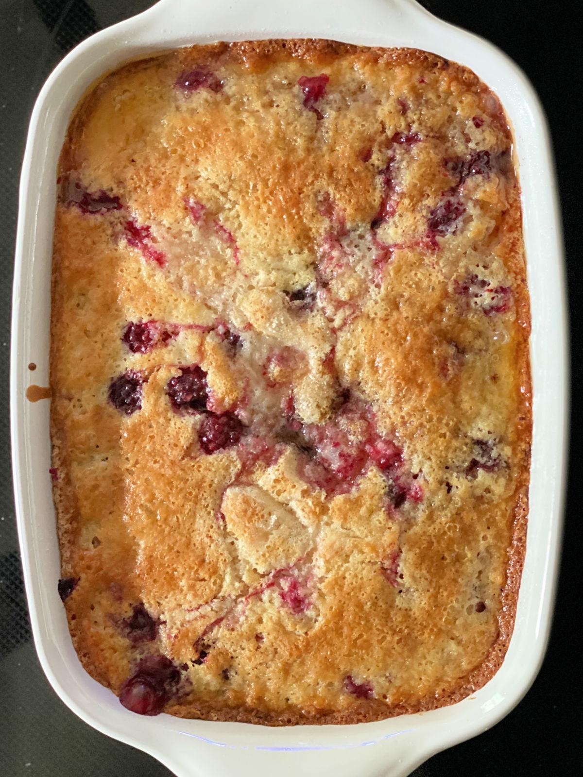 Baked blackberry cobbler in a white rectangle baking dish.
