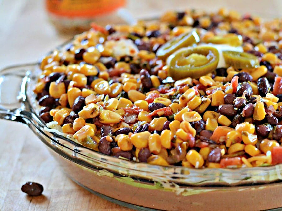 Black bean and corn dip in a glass dish topped with jalapeno slices.