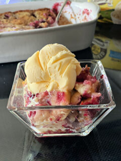 Glass bowl of blackberry cobbler topped with scoop of vanilla ice cream.
