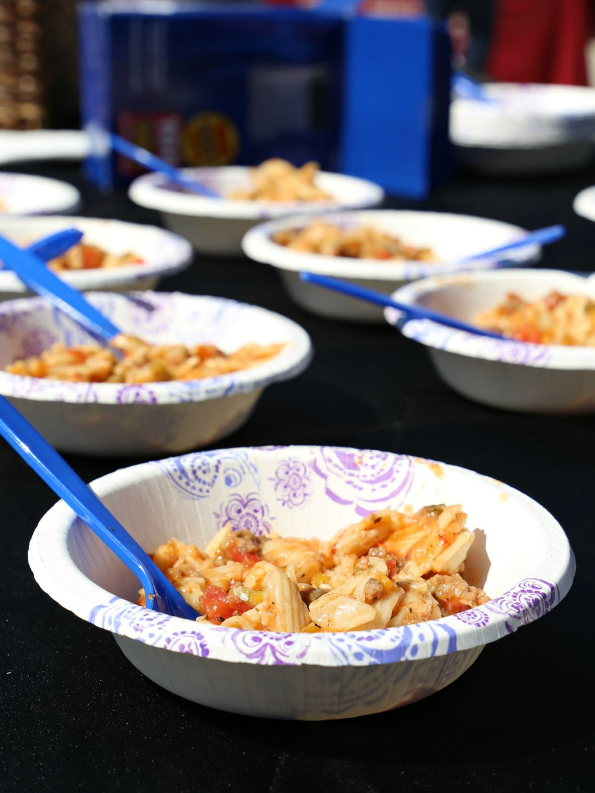 Paper bowls filled with brat stew and blue spoons.