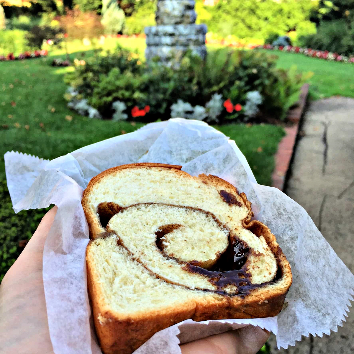 Slice of fresh baked cinnamon bread on parchment paper.