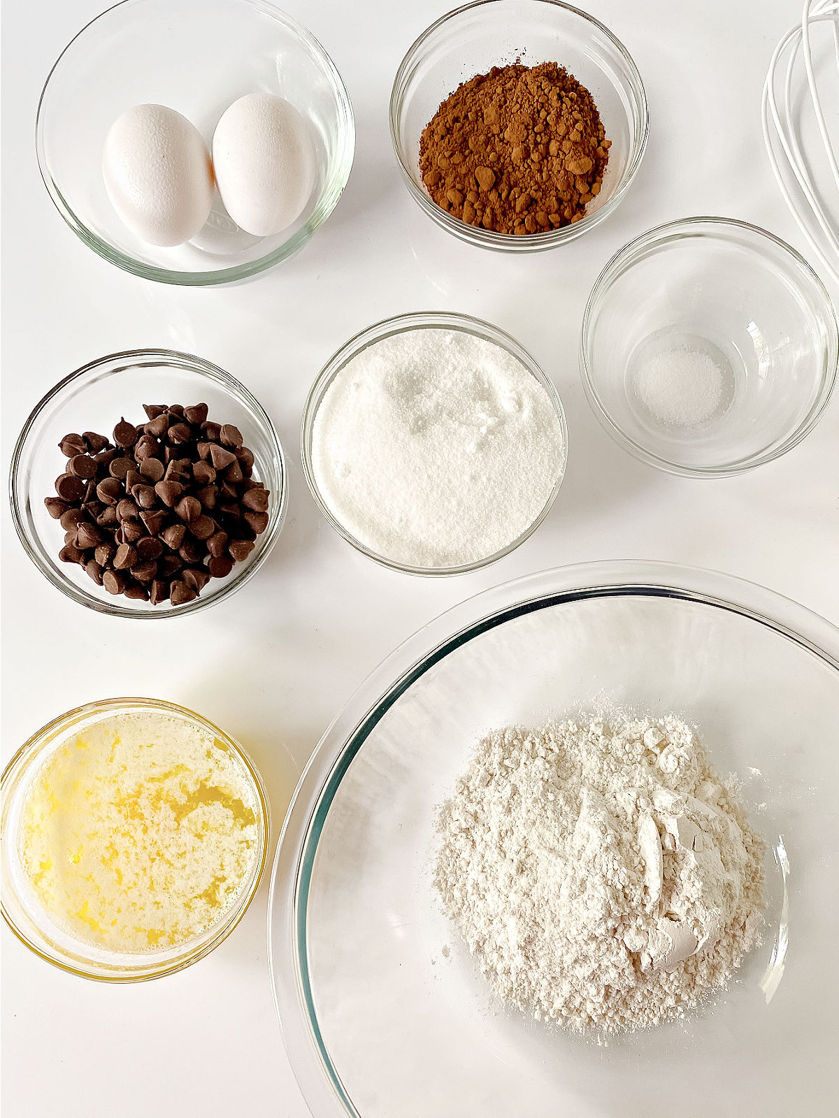 Flour, cocoa powder, sugar, chocolate chips, melted butter, and two eggs in glass bowls.