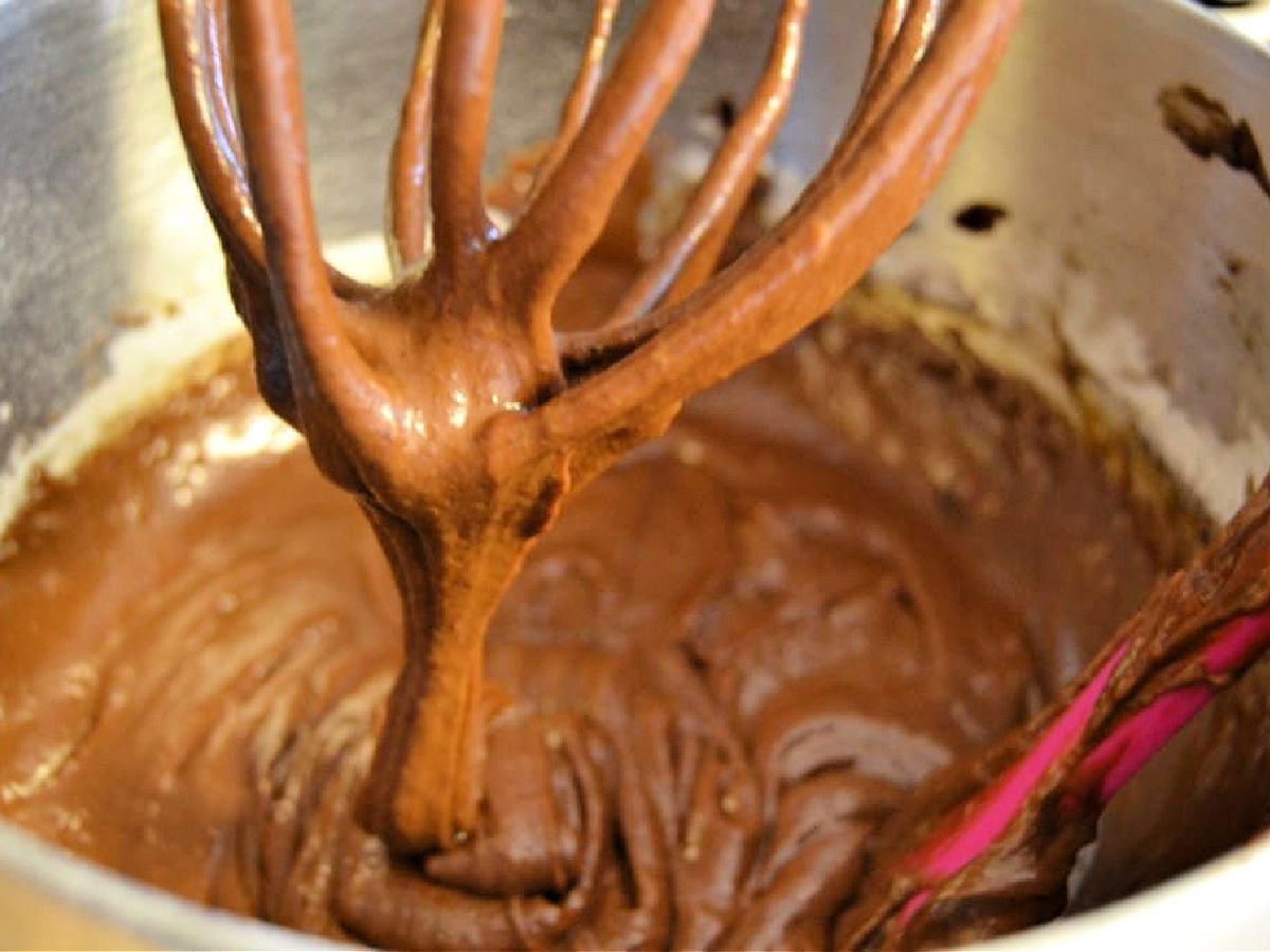 Brownie batter on a whisk attachment in a mixing bowl.