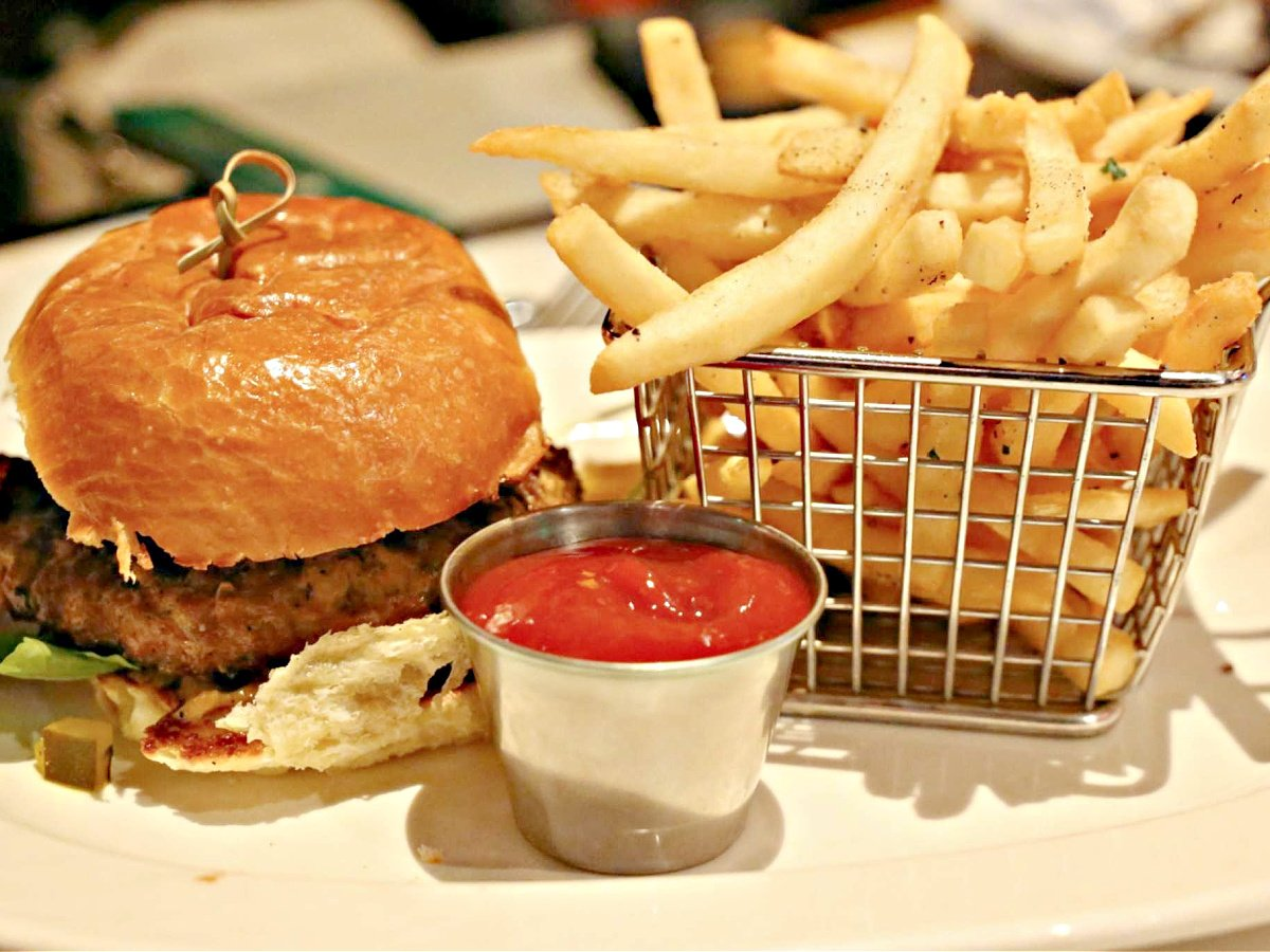 Platter with hamburger, a basket of French fries, and a cup of catsup.