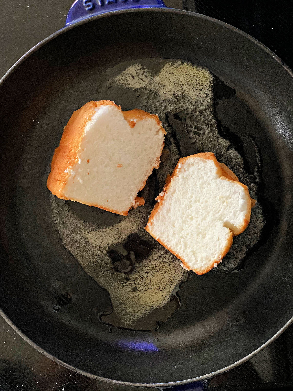 Two slices of angel food cake on melted butter in a skillet.