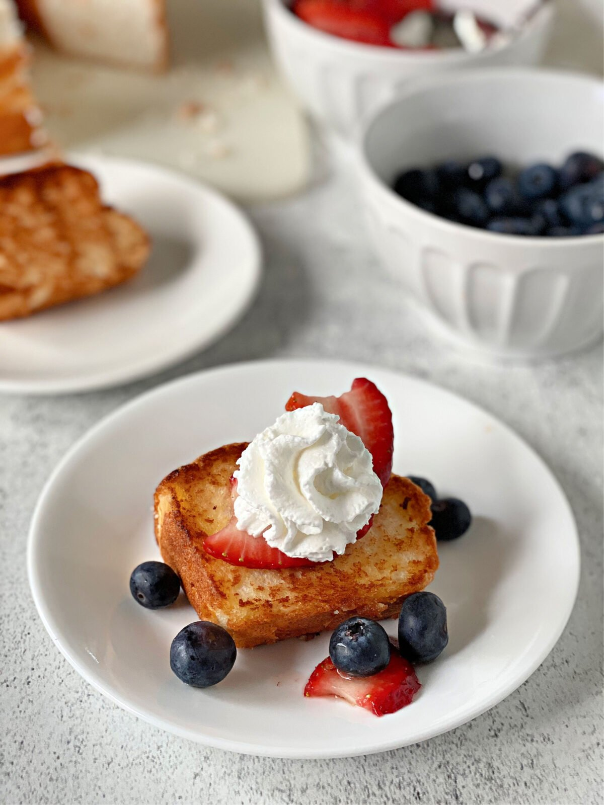 Toasted angel food cake with berries and whipped cream.