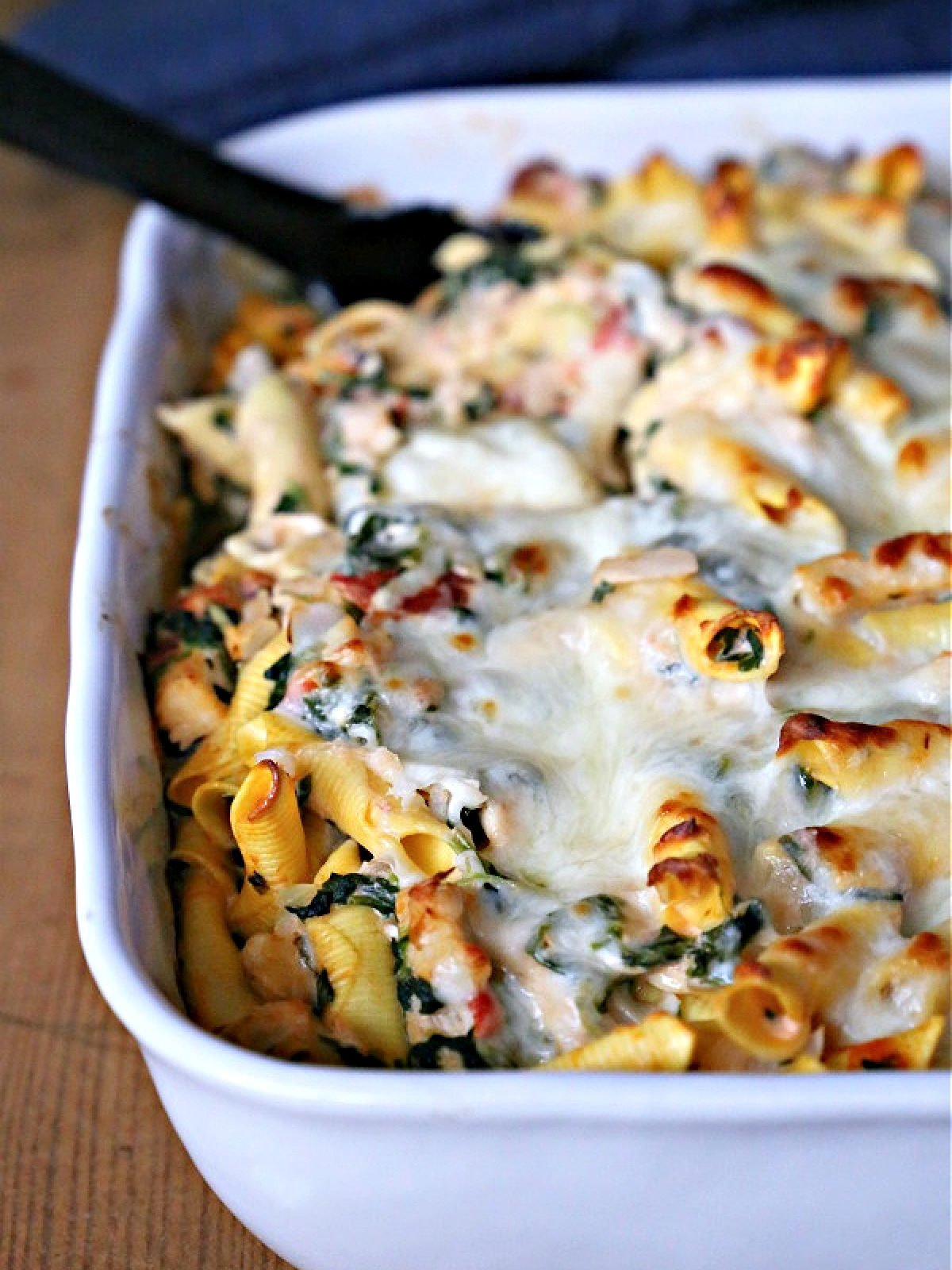 Chicken and spinach casserole in a white baking dish.