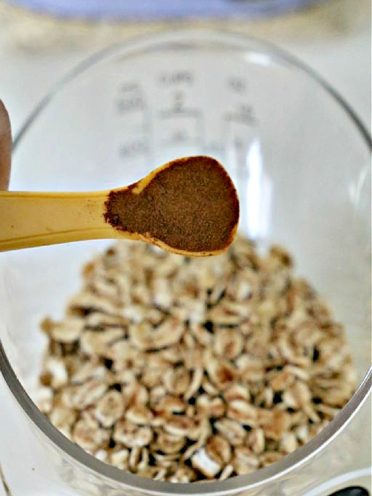 Teaspoon of cinnamon being poured into measuring cup with oats.