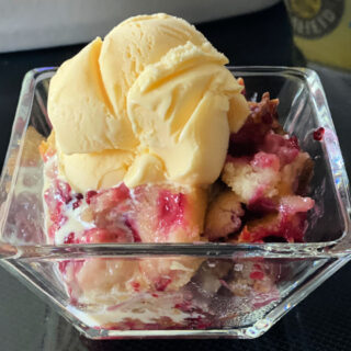 Glass bowl with blackberry cobbler and a scoop of vanilla ice cream.
