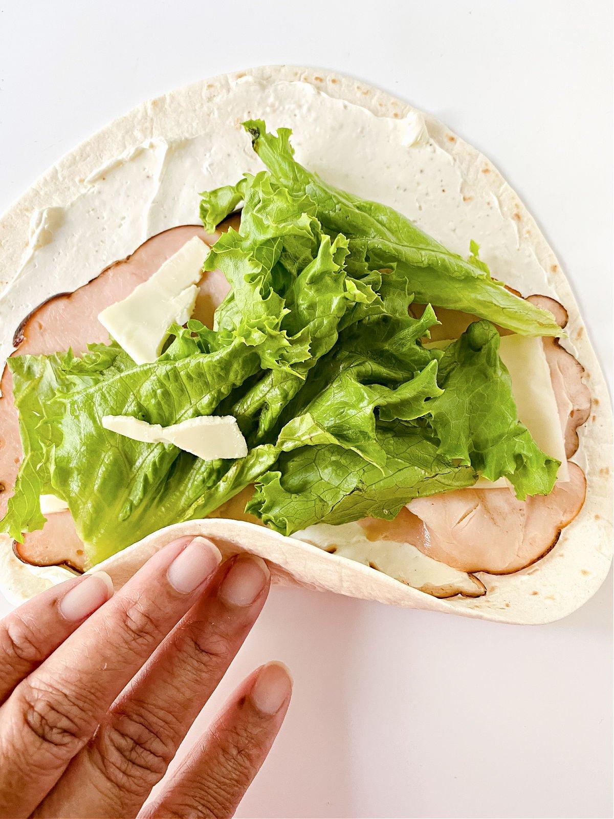 Woman's handing rolling up a flour tortilla sandwich.