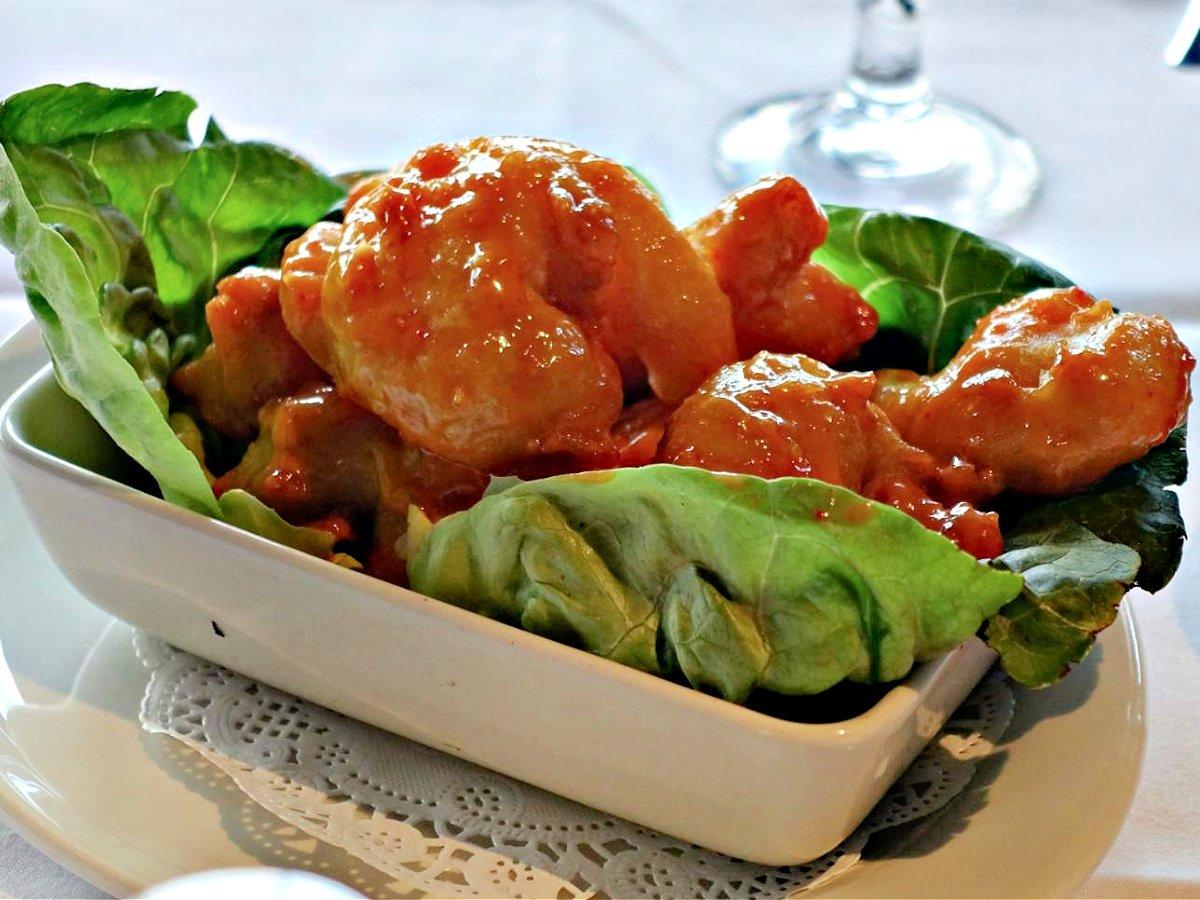 Small bowl of firecracker shrimp on a bed of lettuce.