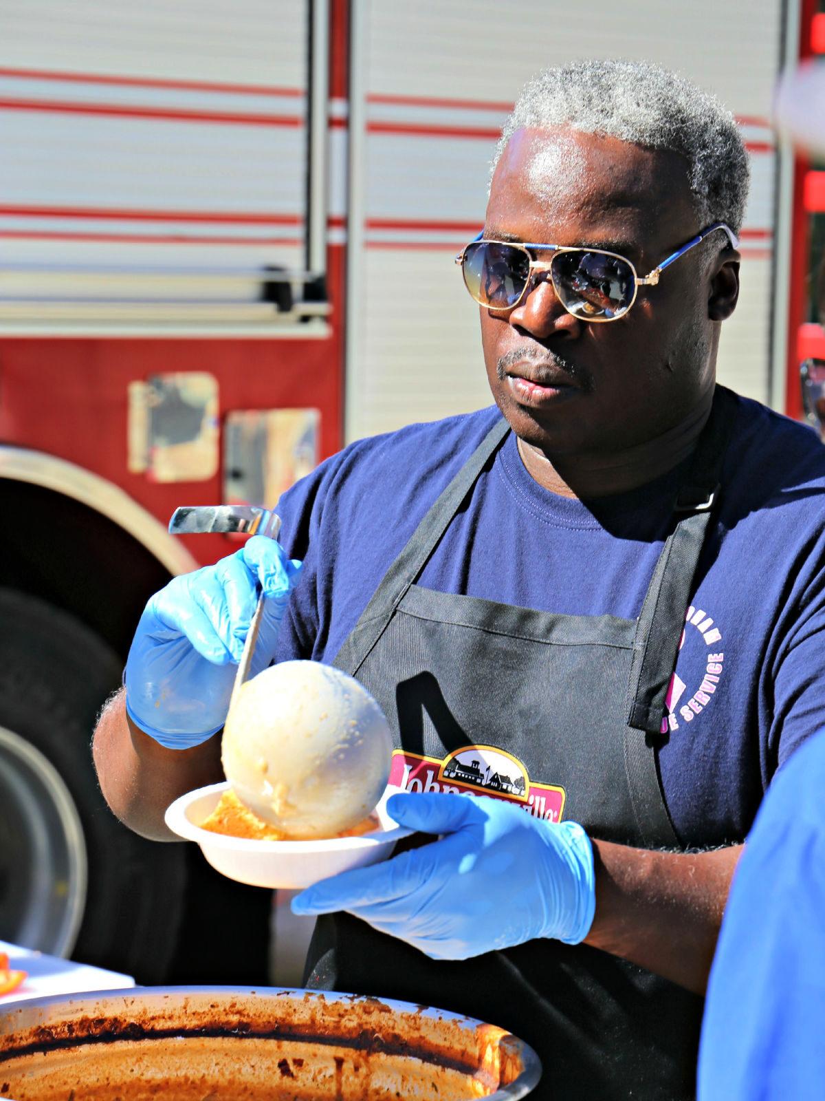 Fireman ladling chili into a bowl.