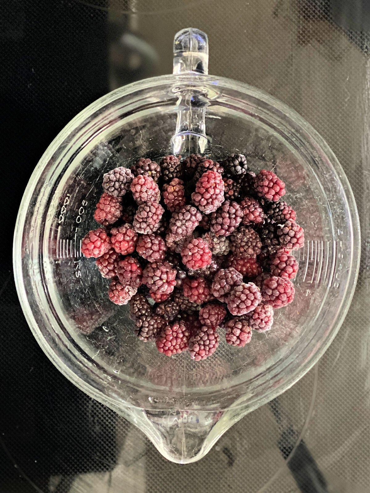 Frozen blackberries in a 2 quart glass measuring cup.