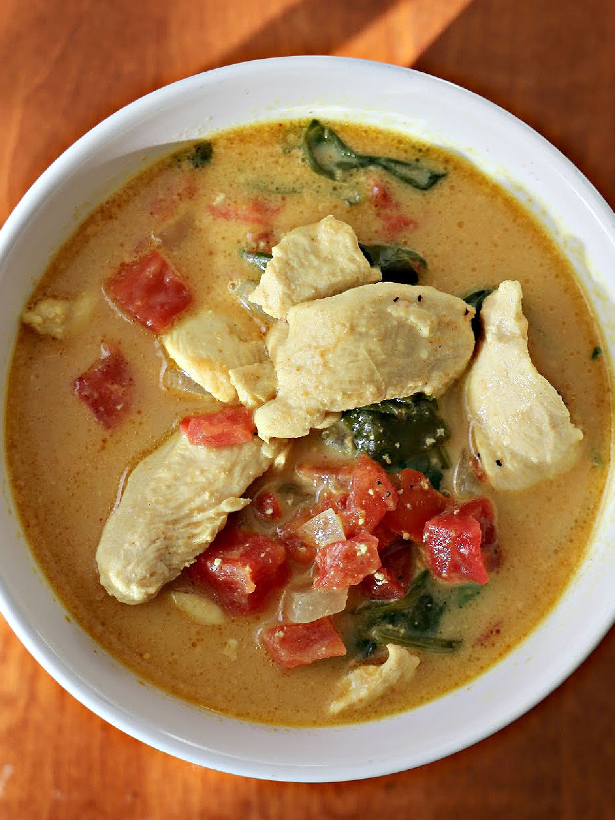 Bowl of chicken curry soup with spinach, tomatoes, and a coconut milk broth.