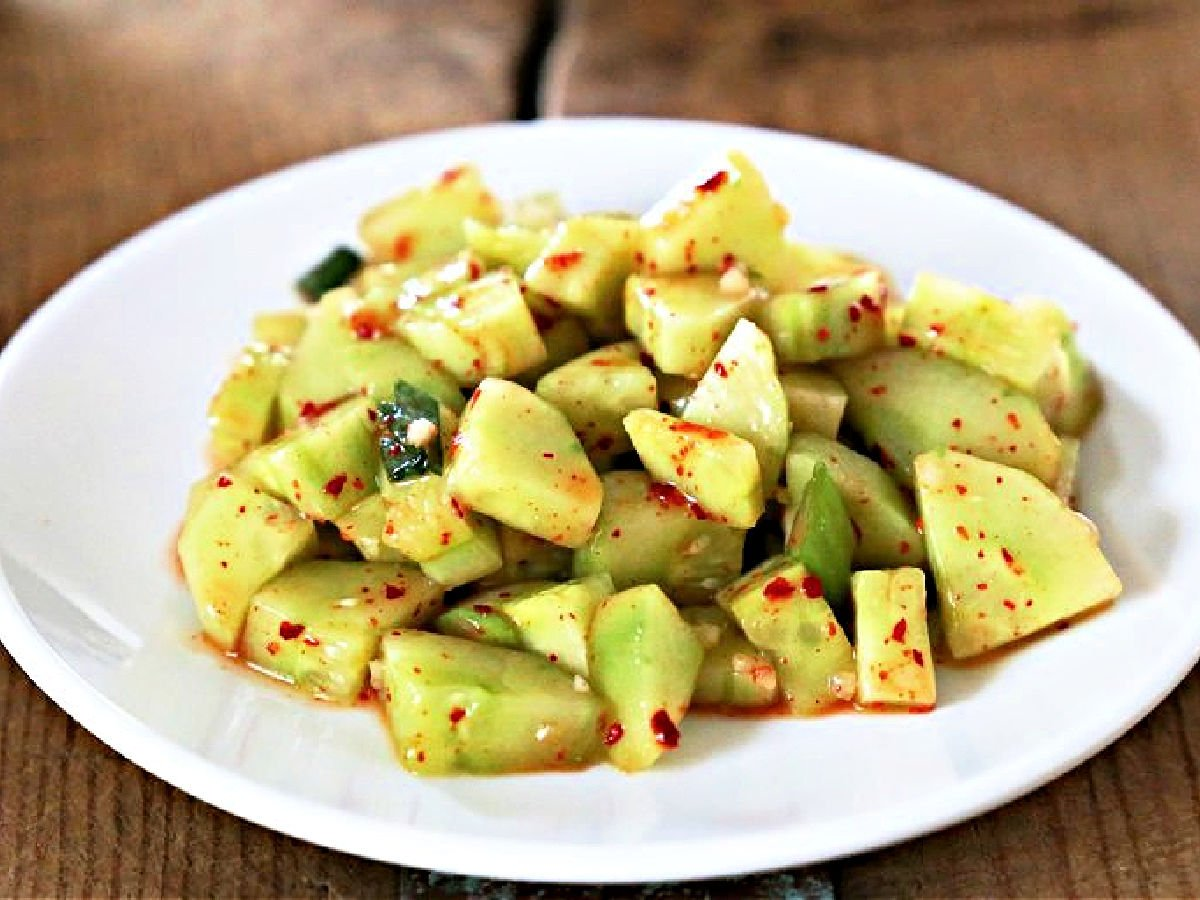 White plate with marinated chopped cucumbers.