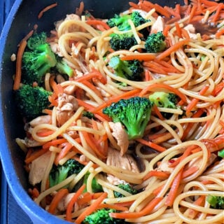 Lo mein with chicken in a black skillet.