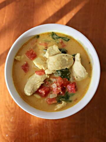 Bowl of chicken curry with diced tomatoes and spinach.