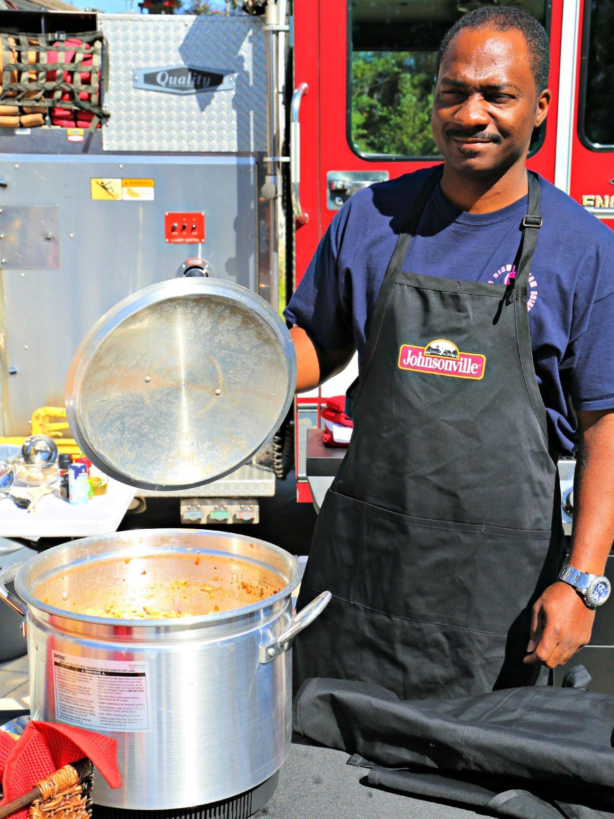 Fireman holding a lid to a stew pot.