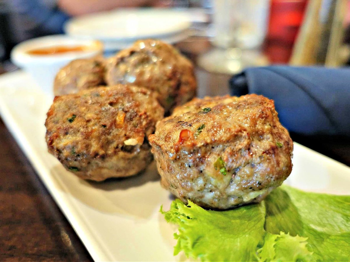 Mozzarella Stuffed Meatballs on a plate with a lettuce leaf.