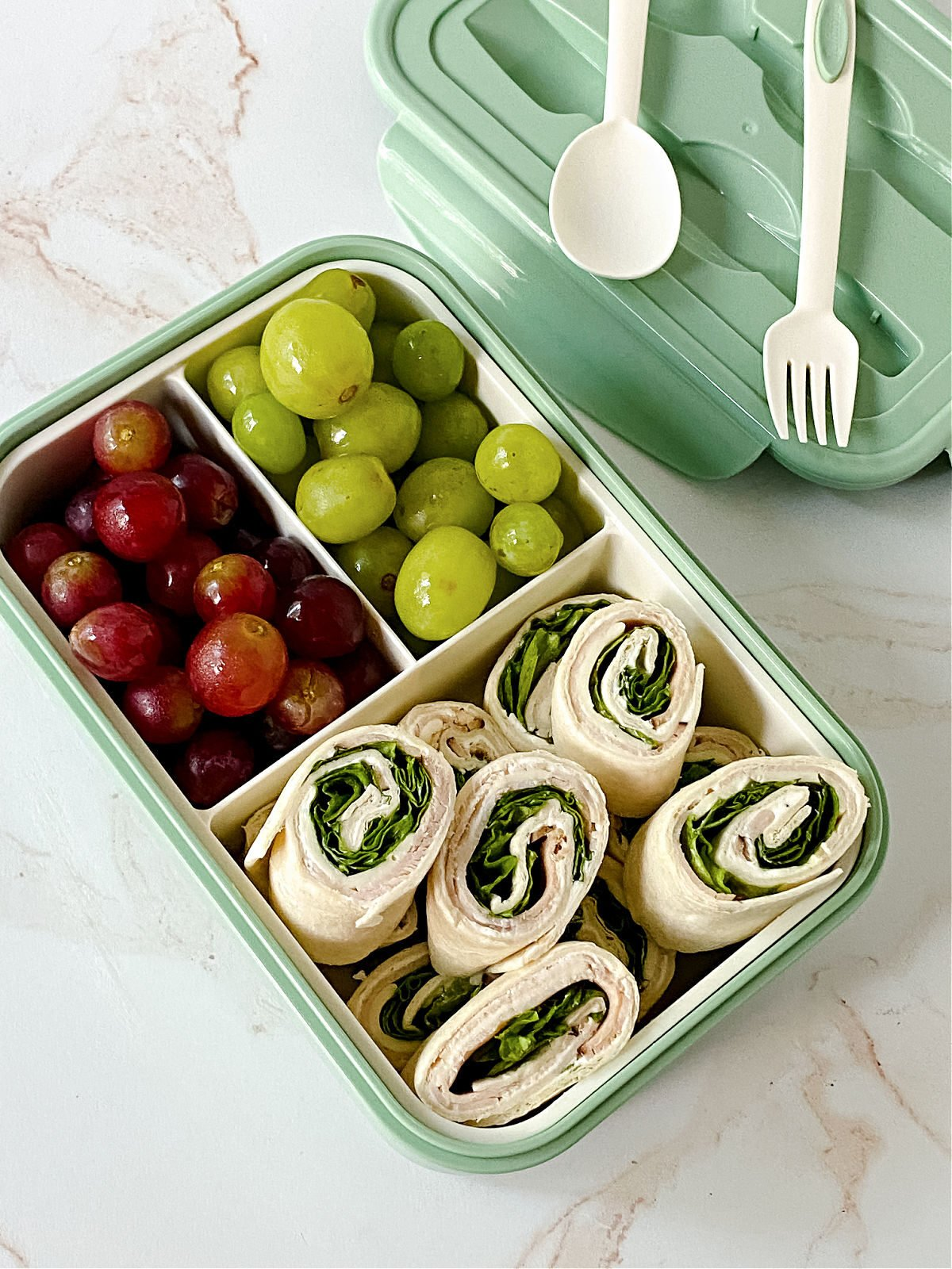 Pinwheel sandwiches and red and green grapes in a bento box.